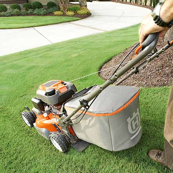 A worker uses a push mower for detailed work