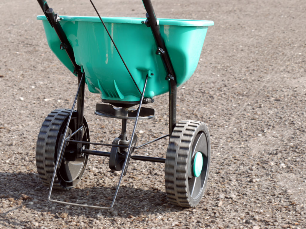 Manually operated seeder filled with grass seeds shot on soil