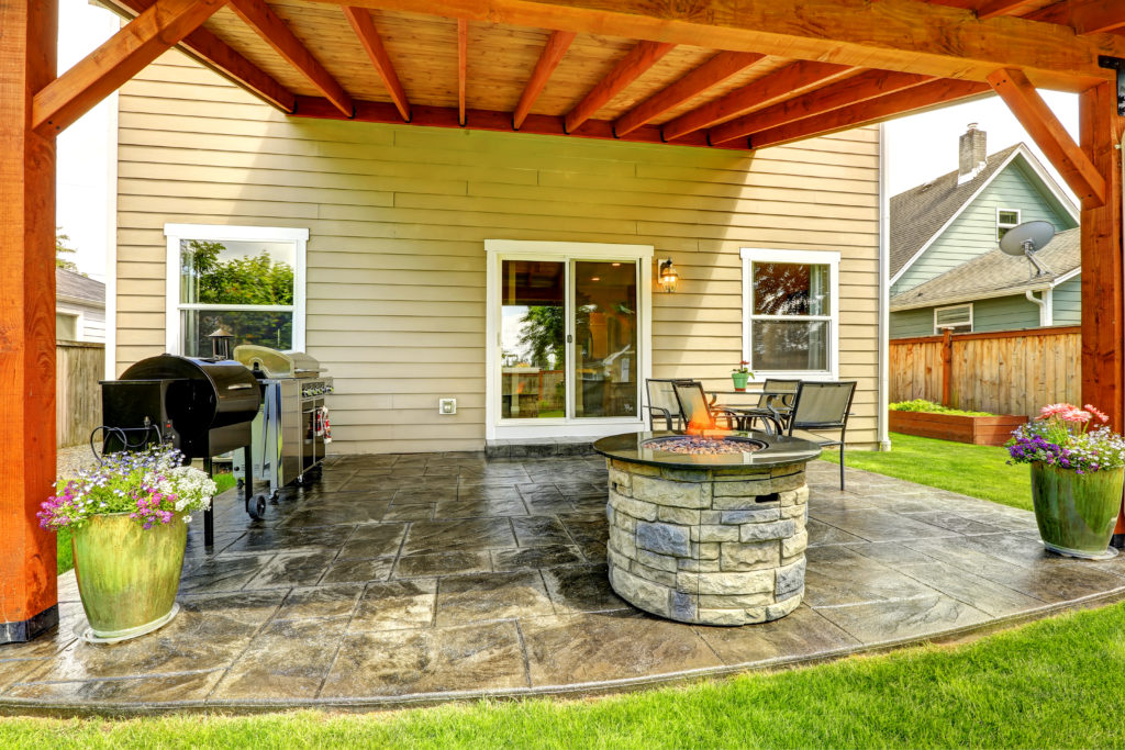 Pergola with patio area. Tile floor decorated with flower pots. Stone trimmed fire pit, patio table set and barbecue