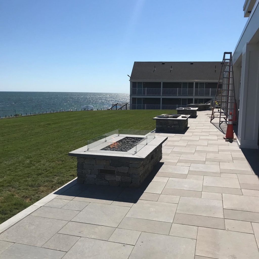 A large patio and several firepits by the green lawn