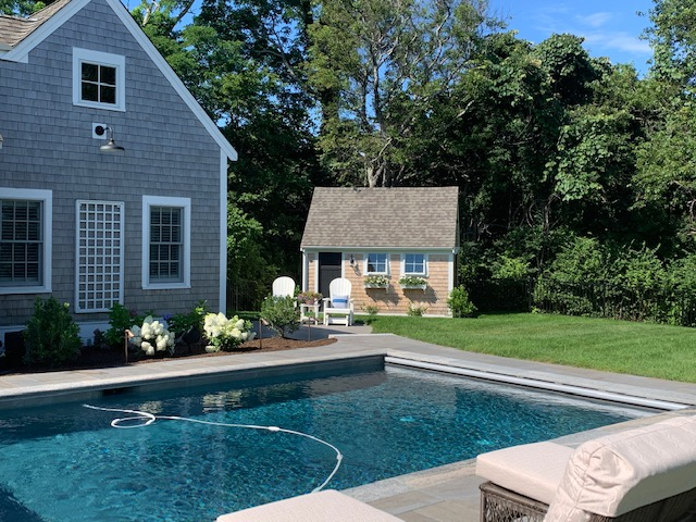 A pool with hardscaping and a cute shed on a lawn on Cape Cod