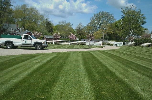 Cooper Landscaping truck with a perfectly mowed lawn