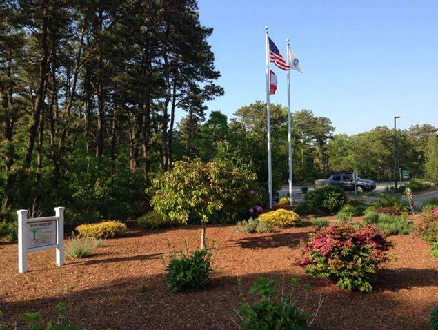 A mulched area outside the Yarmouth Police Department with shrubs and American flag