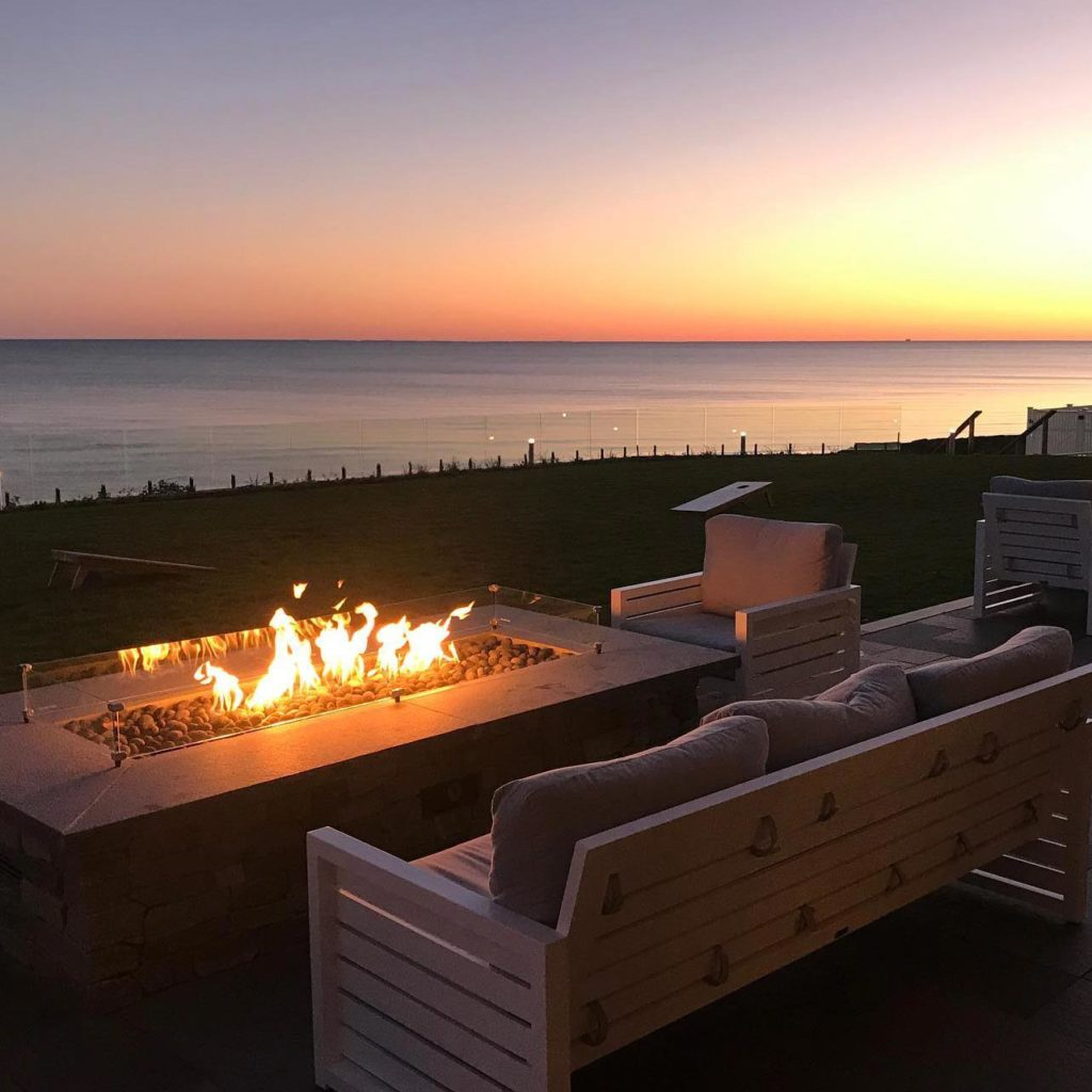 A beautiful sunset over the ocean with a firefit roaring in the foreground