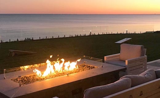 Outdoor gas firepit with an ocean sunset in the background